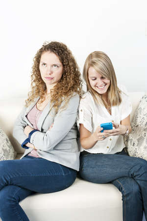 bad manners: Young woman ignoring her friend checking smart phone breaching cellphone etiquette