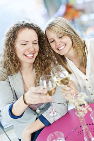 Two happy women celebrating with glasses of white wine photo