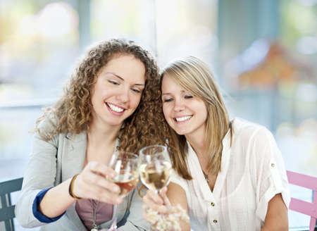 Two happy women in cafe celebrating with glasses of white wine photo