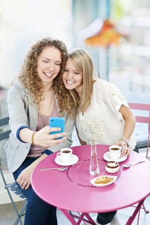 Two smiling women looking at smart phone in cafe