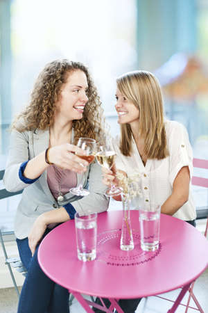 Two happy women celebrating with glasses of white wine in cafe photo