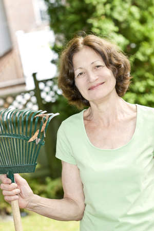 Senior woman smiling holding rake and gardening outside photo