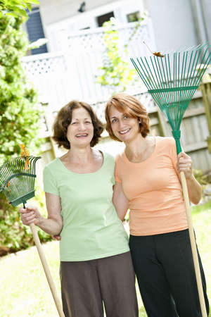 Mother and daughter holding rakes gardening outside photo