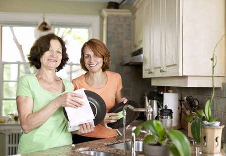 Mother and daughter doing dishes in kitchen at home Stock Photo - 12922954