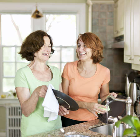 Mother and daughter doing dishes in kitchen at home photo