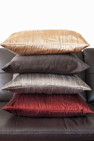 seating furniture: Four colorful cushions stacked on dark brown leather couch Stock Photo