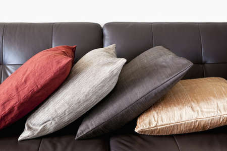 Four colorful cushions on dark brown leather couch Stock Photo - 12922983