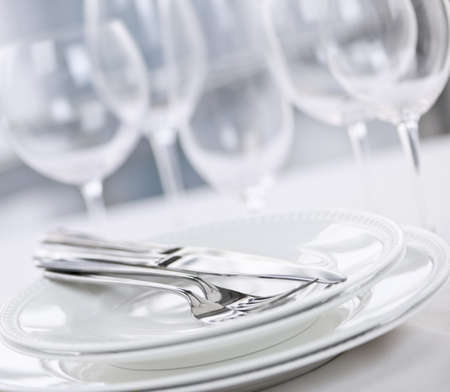 stemware: Elegant restaurant table setting with plates cutlery and stemware Stock Photo