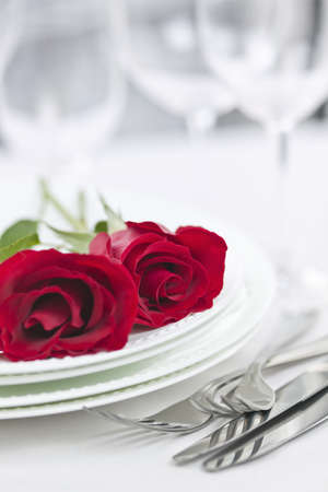 Romantic table setting for two with roses plates and cutlery photo