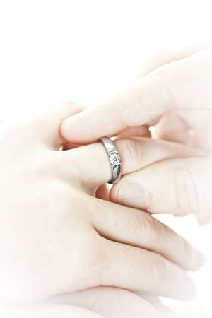 Closeup of hands placing engagement ring on finger photo