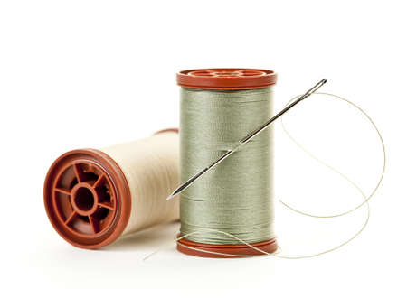 tailoring: Two spools of thread with needle for sewing isolated on white background