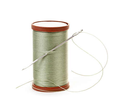 equipment: Spool of thread with needle for sewing on white background