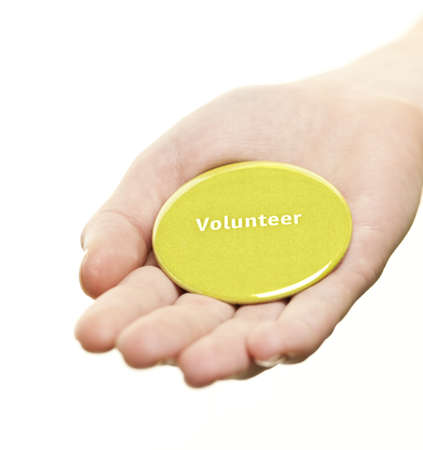 Hand holding green round volunteer button isolated on white