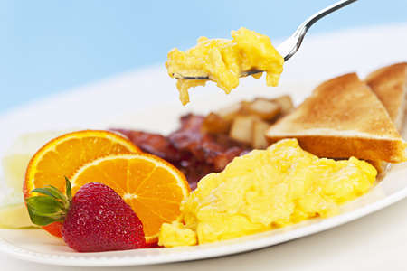 Scrambled eggs on a fork above breakfast plate with fruits toast and bacon