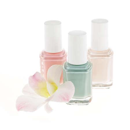 白い背景の上の蘭の花と 3 つのマニキュア ボトル
