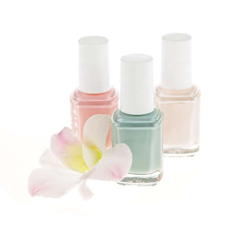 Three nail polish bottles with orchid flower on white background