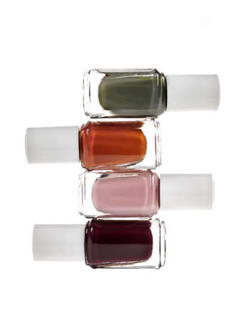 cosmetic lacquer: Nail polish bottles of various colors stacked isolated on white background Stock Photo