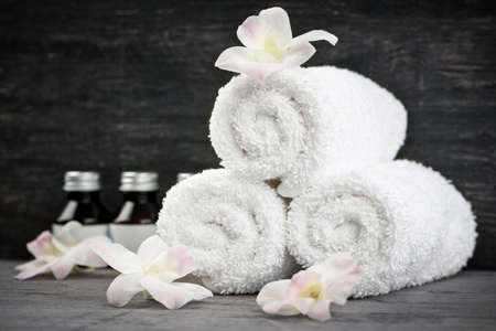 White rolled up towels with body care products at spa Stock Photo - 13306548