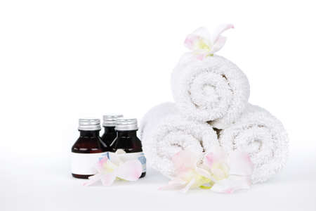 towels luxury: White rolled up spa towels and body care products with orchid flowers Stock Photo