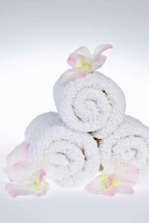White rolled up spa towels with orchids flowers Archivio Fotografico