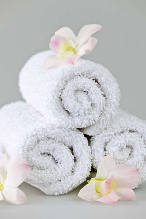 towels luxury: White rolled up spa towels with orchids flowers Stock Photo