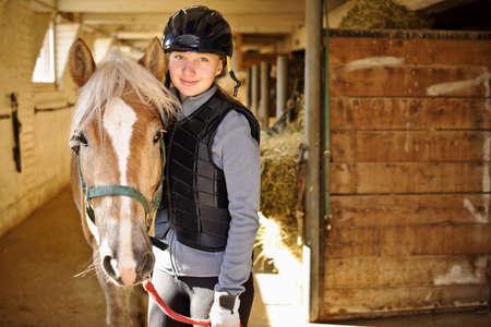 Portret van tiener meisje met paard in stal Stockfoto