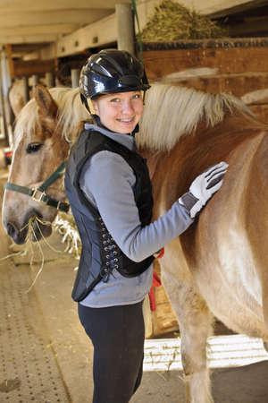 riding helmet: Retrato de ni�a adolescente con el caballo en el establo