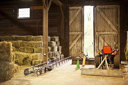 wood agricultural: Interior of wooden barn with hay bales stacks and farm equipment Stock Photo