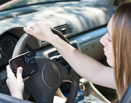 Teenage girl texting on cell phone while driving Imagens - 14347044