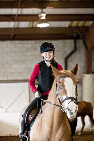 Teenage girl on horseback wearing helmet and safety vest in indoor arena
