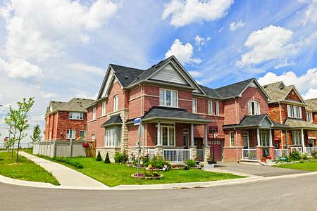 rij huizen: Suburban residentiële straat met rode bakstenen huizen Stockfoto