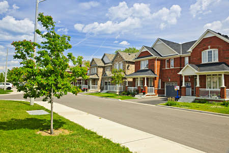 housing development: Suburban residential street with red brick houses Stock Photo