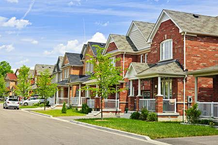 residential neighborhood: Calle de los suburbios residenciales con casas de ladrillo rojo