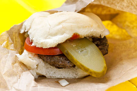 Homemade hamburger with pickle and tomato in paper wrapper Stock Photo - 15059607
