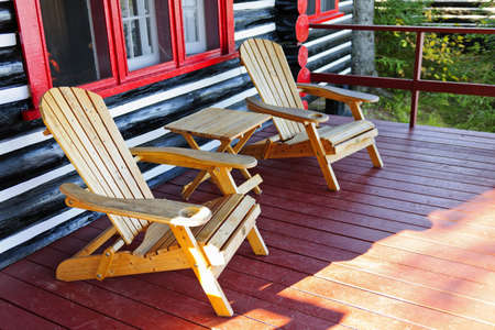 Wooden log cabin cottage porch with adirondack chairs photo