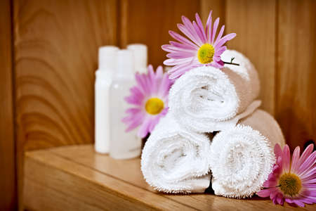 spa towels: White rolled up spa towels with body care products Stock Photo