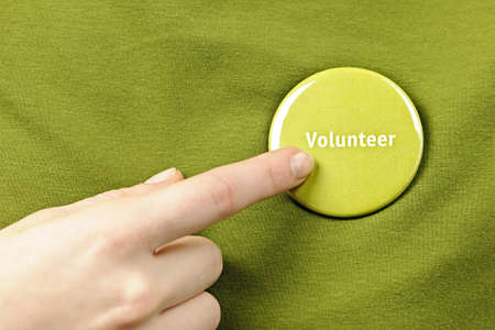 Finger pointing to green round volunteer button photo
