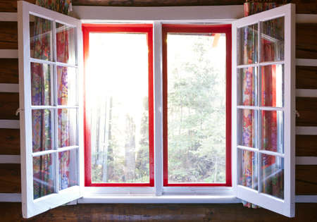 Open windows in cottage with sunshine and view of forest photo