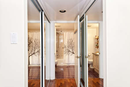 closet: Interior hallway with walk through mirrored closets to bathroom Stock Photo