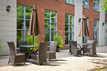 Patio furniture with umbrellas on stone patio near upscale condo building Stock Photo - 15391766
