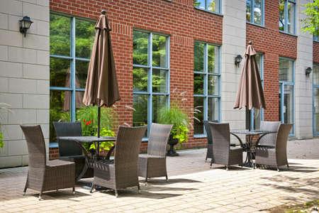 Patio furniture with umbrellas on stone patio near upscale condo building Stock Photo - 15391766