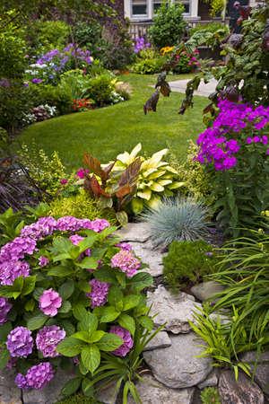 화와 다채로운 식물 무성한 아름다운 정원 스톡 콘텐츠