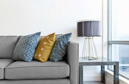 El diseño interior con un sofá, cojines de colores y una lámpara en la mesa final Foto de archivo