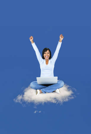 com: Happy black woman with computer sitting on cloud