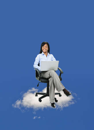 Smiling black businesswoman sitting in office chair on cloud with laptop computer photo