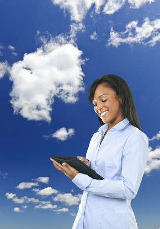 tablet: Smiling black woman with tablet computer over clouds and blue sky