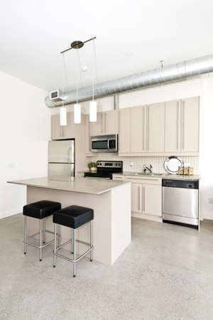 Kitchen in modern loft condo with island and stainless steel appliances Stok Fotoğraf