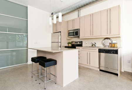 Kitchen in modern loft condo with island and stainless steel appliances Stock Photo