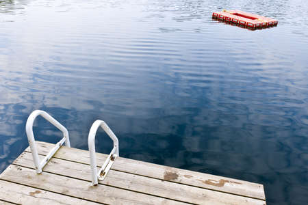Dock and ladder on calm summer lake with diving platform in Ontario Canada Stock Photo - 15898727