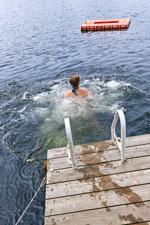 Teen girl splashing and swimming in lake near dock Stock Photo - 15891795